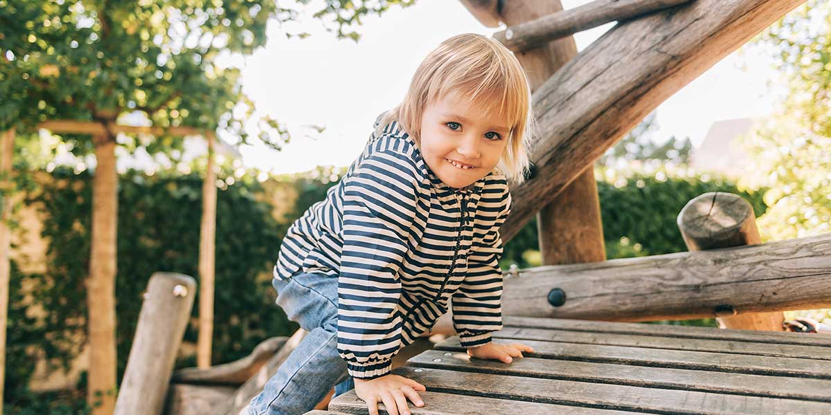 Ein kleines Kind spielt an einem Holz-Klettergerüst.